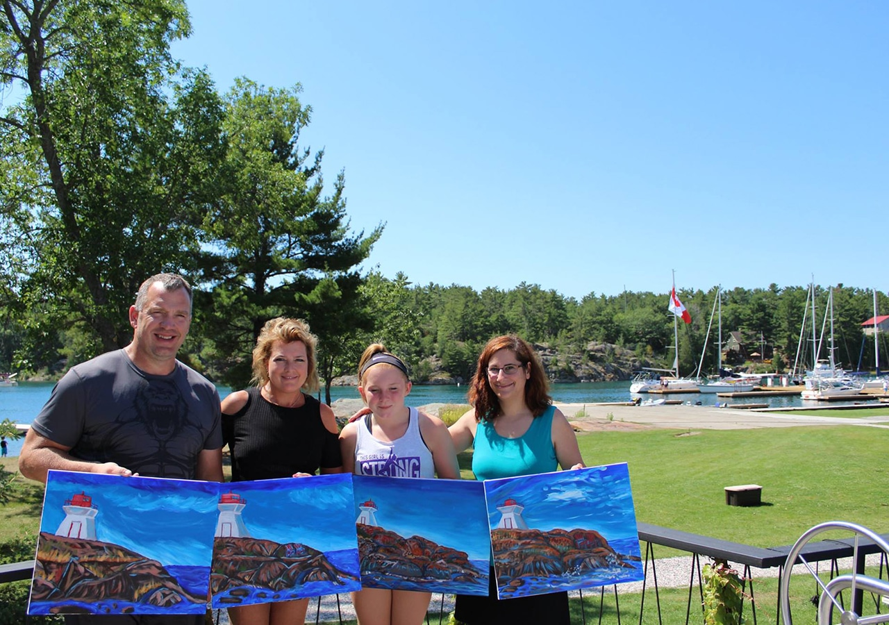 Family with paintings of lighthouse